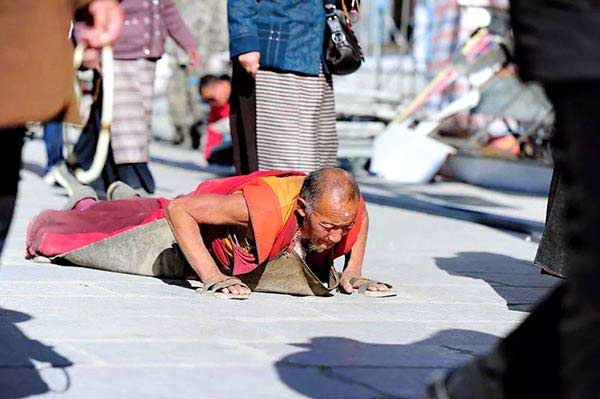 Tibetan pilgrims doing prostration ritual on Barkhor Street