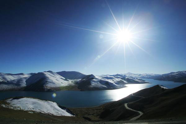 Yamdrok Lake surrounded by snow-capped mountains